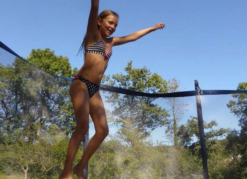 Petite fille qui fait du trampoline au camping le plo
