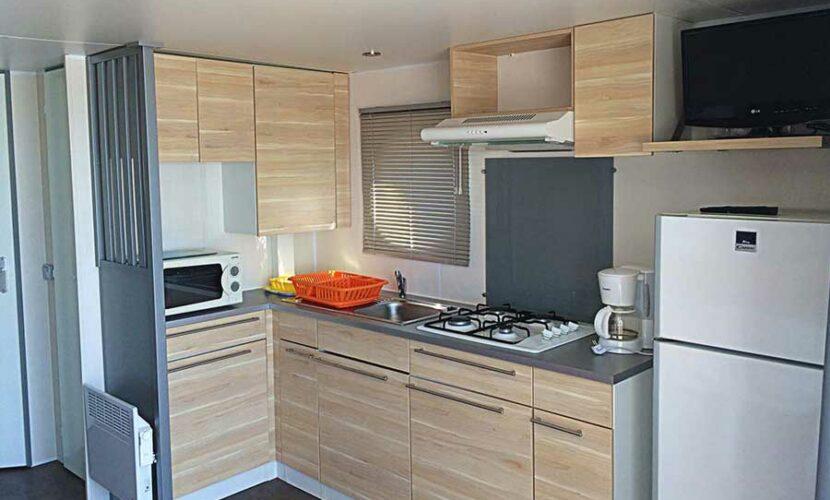 Coin cuisine et frigo d'un mobil-home au camping les violettes