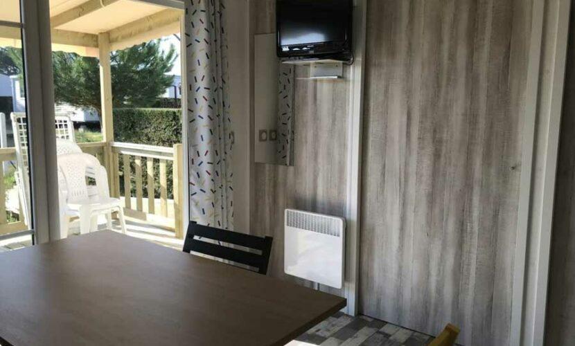 Salon avec télé d'un mobil-home PMR au camping les violettes