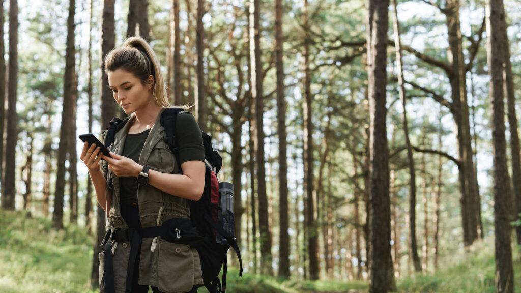 Une randonneuse cherche l'inspiration sur une appli mobile